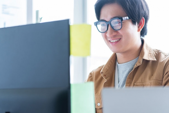 Young graduate male using laptop wearing glasses